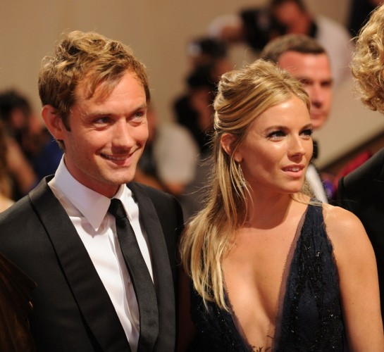 Jude Law and Sienna Miller standing next to each other on a red carpet.