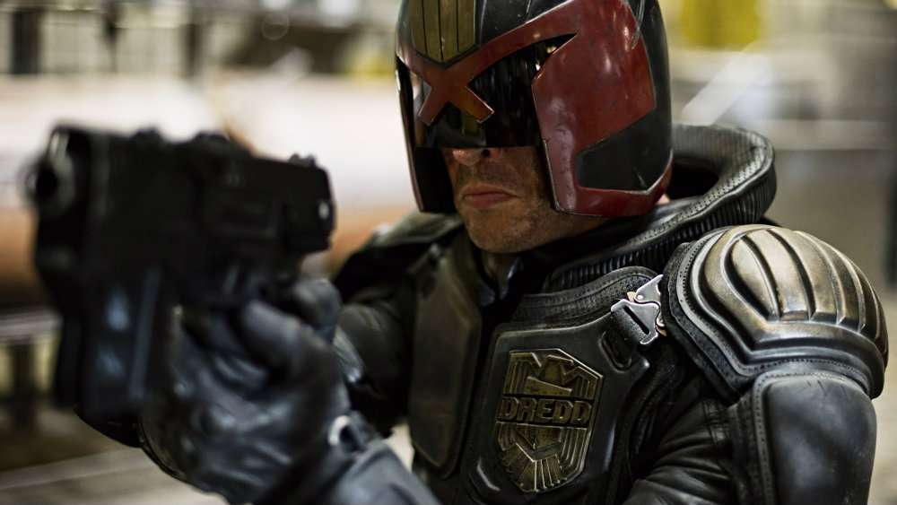 Karl Urban in Dredd holds a gun while in his suit and mask