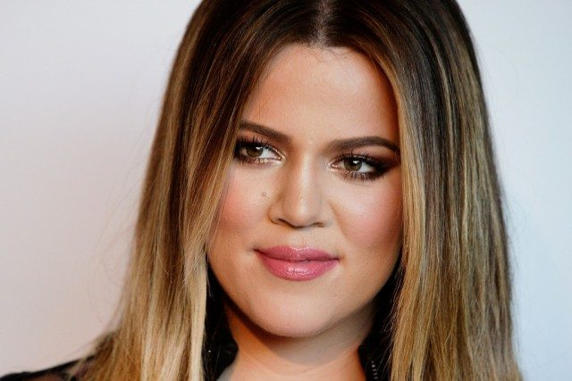 Khloe Kardashian smiling while in front of a white wall.