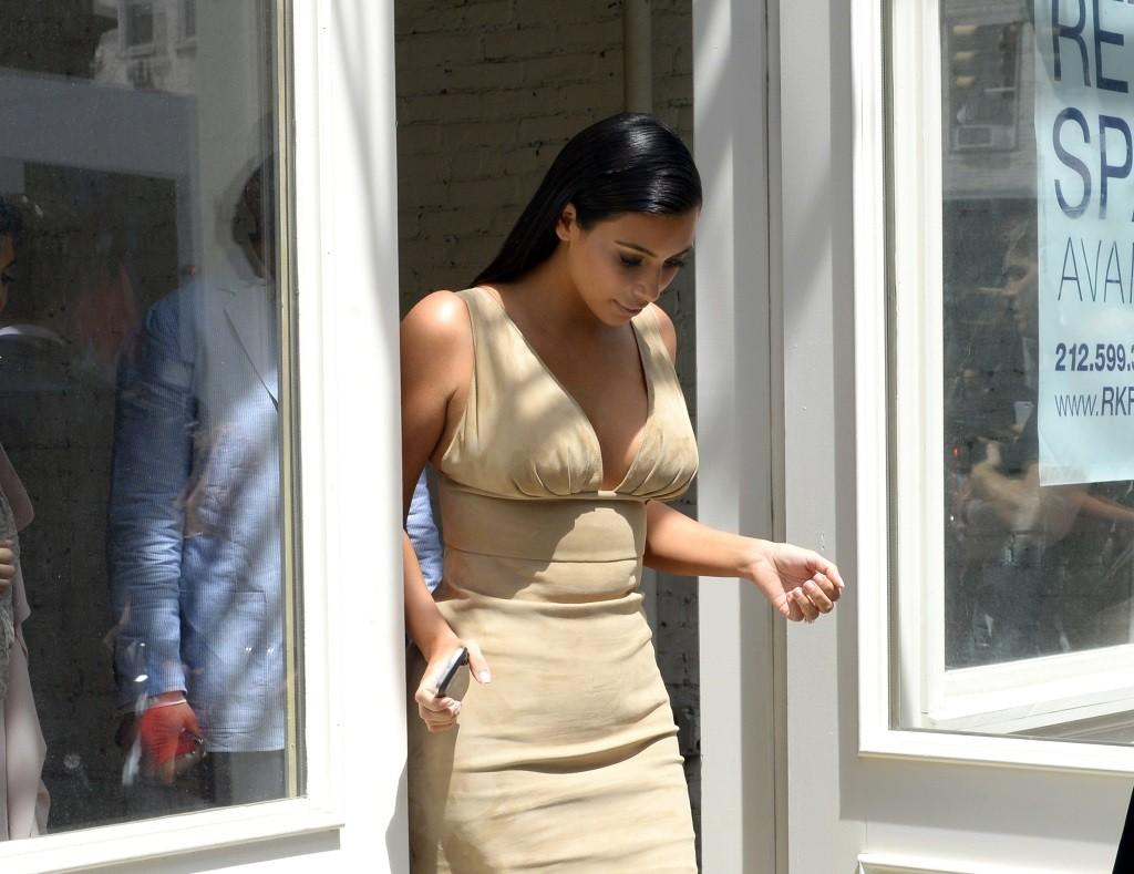 Kim Kardashian looking down in a tan dress