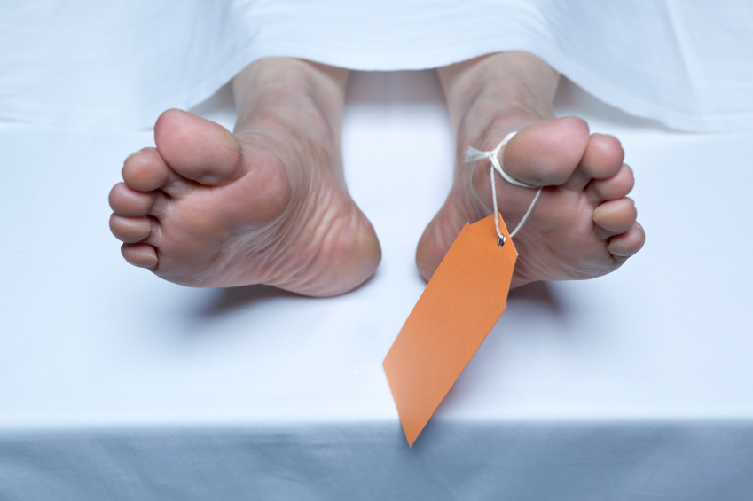 feet of a deceased person with an orange tag on a table at the morgue