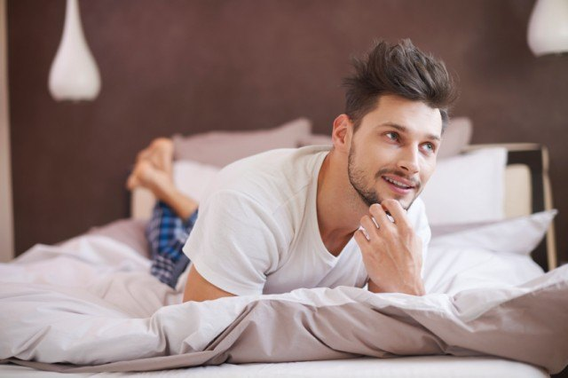 young man smiles as he lounges on his stomach in bed