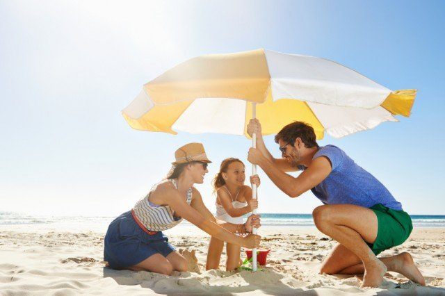 family of three setting up a beach umbrella to limit sun exposure on a sunny day at the beach