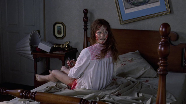 Linda Blair in The Exorcist is sitting on her bed and her head is completely turned around.