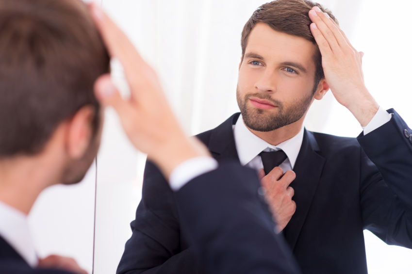 young attractive man looking at himself in mirror
