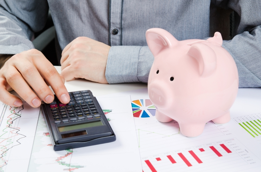 Man calculates money on calculator along with piggy bank