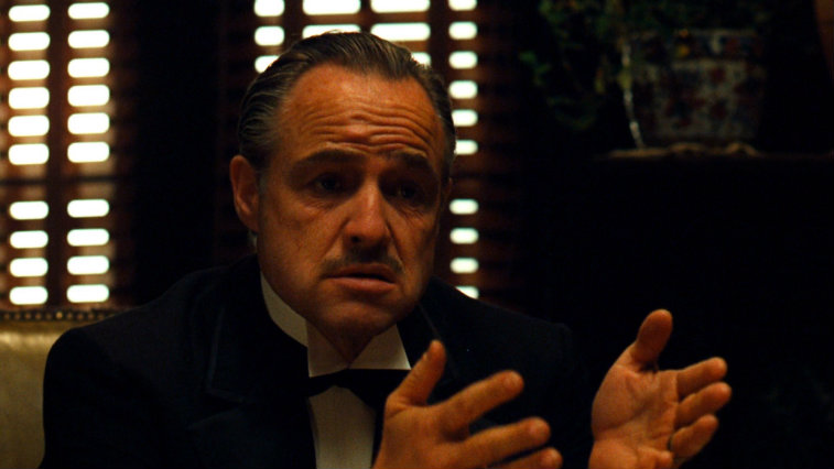 Marlon Brando sitting in a darkened room with his hands out in The Godfather