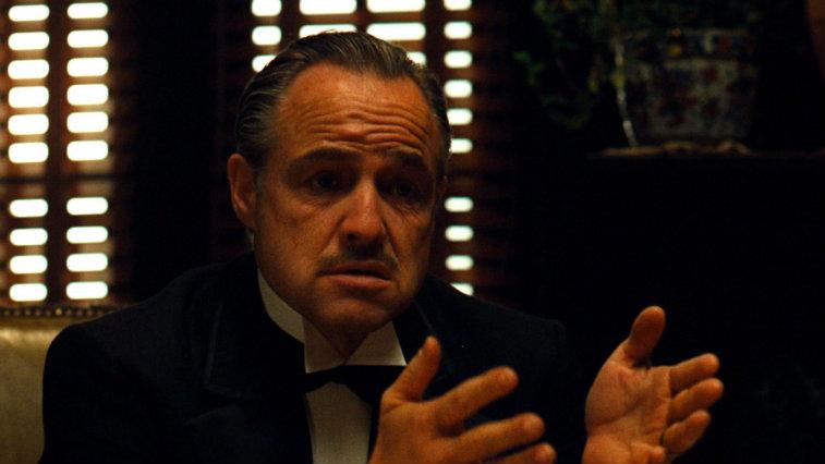 Marlon Brando sitting in a darkened room in The Godfather