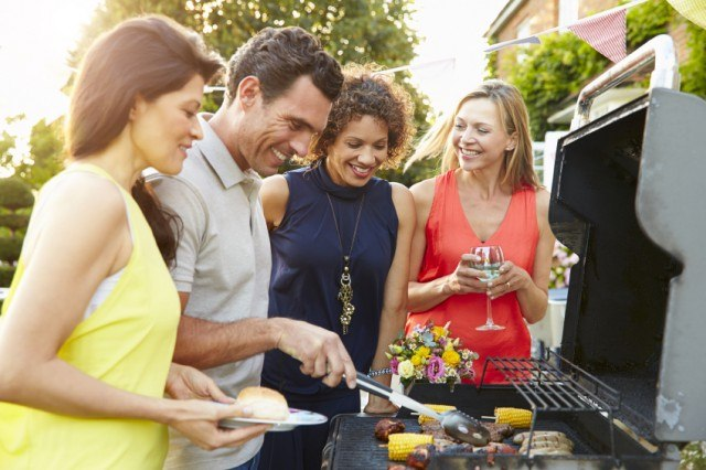 Friends hanging out around the grill at a cookout