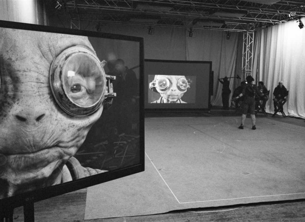 Maz Kanata on a pair of large screens in an otherwise empty studio