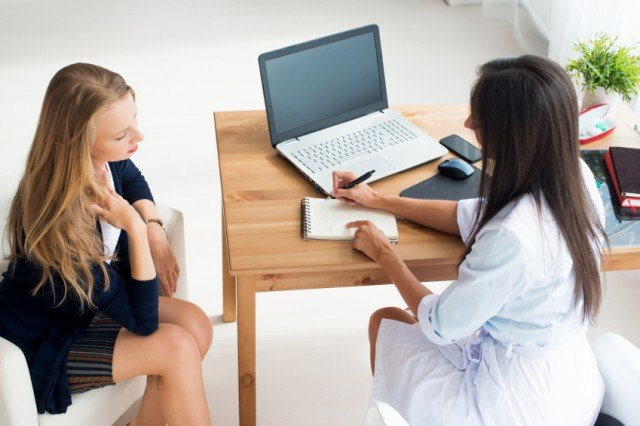 A woman sits across from her doctor in a medical office
