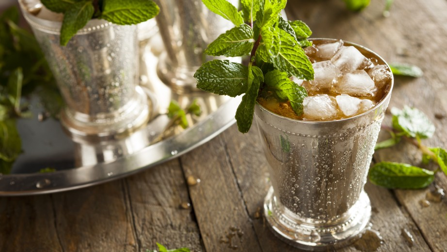 ming julep in a silver cup on a wooden table