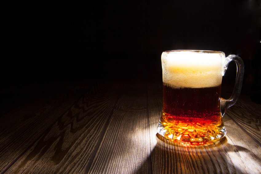 mug of beer sitting on a wooden counter in low lighting
