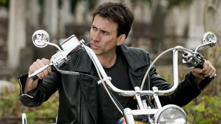 Nicolas Cage is looking to one side and sitting on a motorcycle in Ghost Rider.