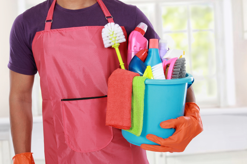 man holding cleaning products in his house