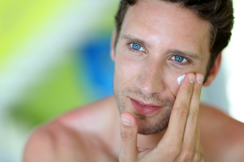 young man applying cream on his face