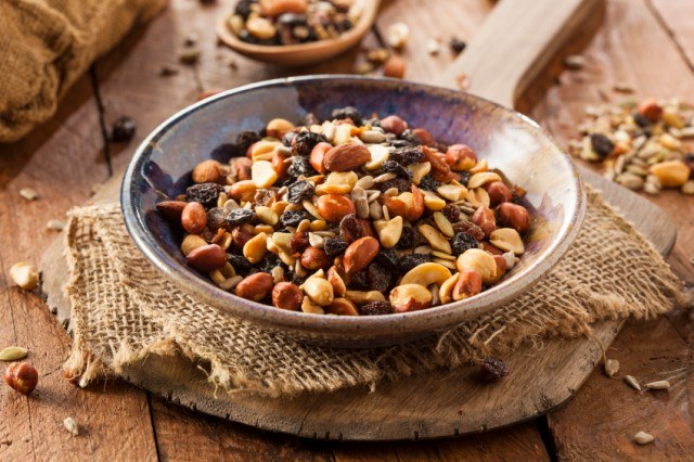 bowl overflowing with homemade trail mix made with nuts, seeds, and dried fruit
