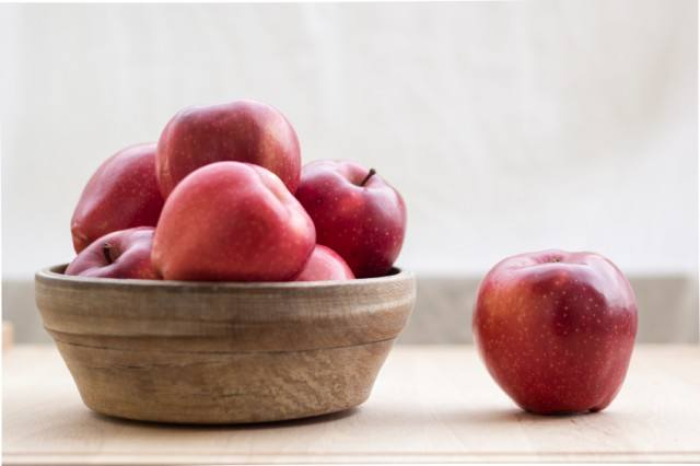 Red apples in wooden bowl