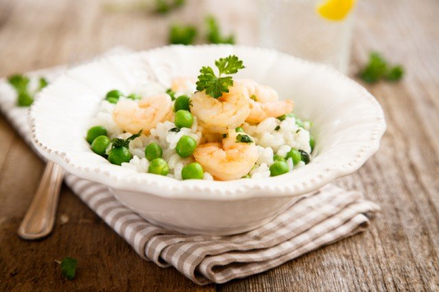 fancy white bowl filled with rice, green peas, and rice
