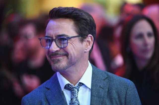 Robert Downey Jr. smiles while wearing glasses and a suit.