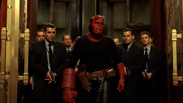 Ron Perlman as Hellboy stands in front of a group of men in suits with guns in Hellboy II The Golden Army