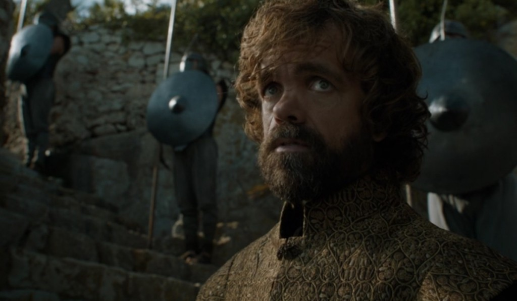 Tyrion with a beard, looking up slightly while wearing a brown tunic