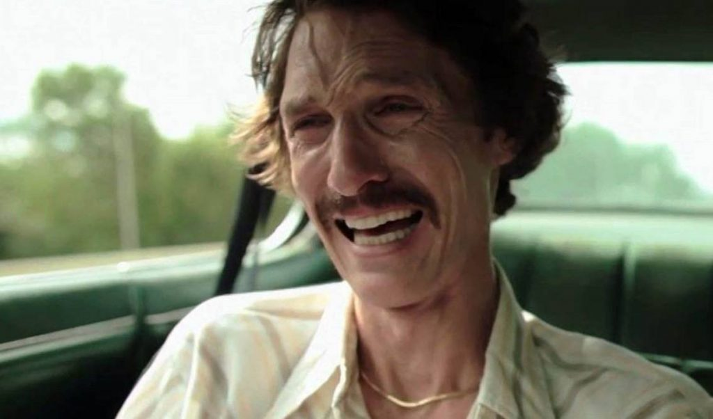 Matthew McConaughey with a mustache, crying in the front seat of a car