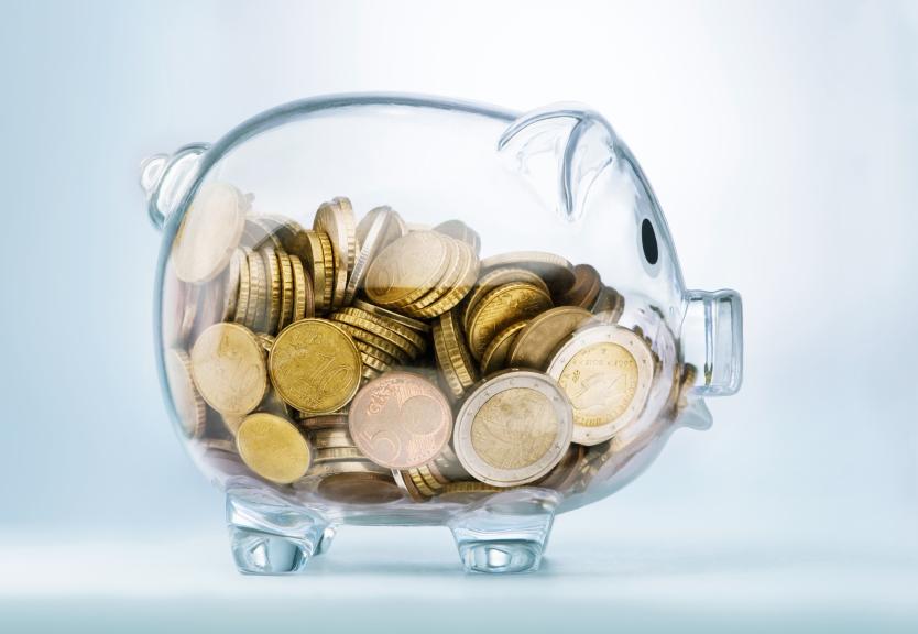 a glass see through piggy bank full of coins