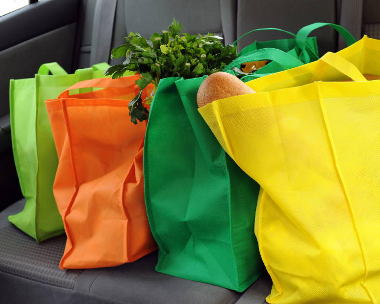four reusable shopping bags filled with grocereis