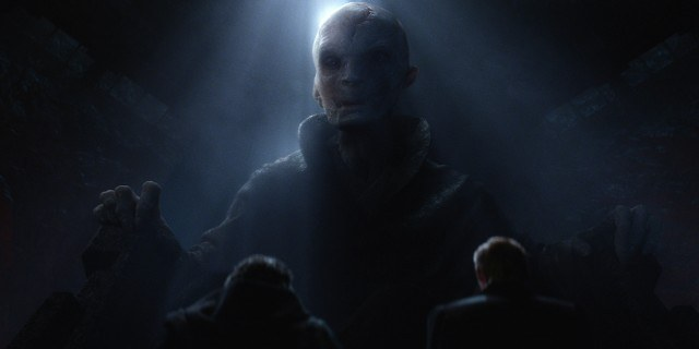 Supreme Leader Snoke, half-lit, sits in a large chair, looking down at the camera.