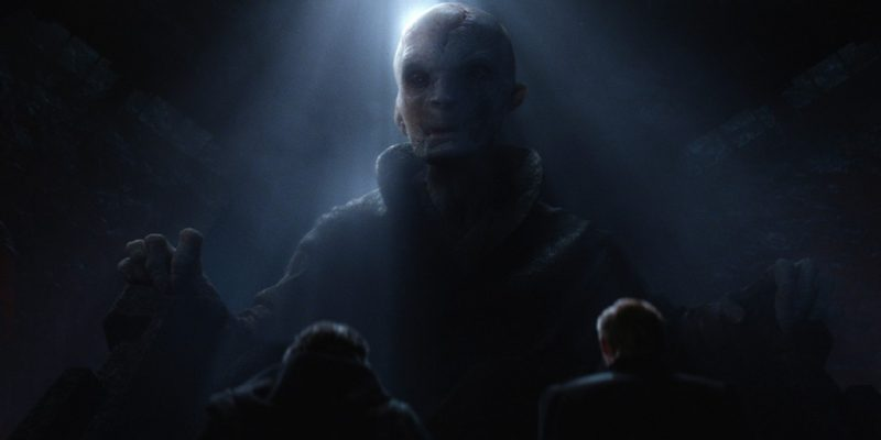 Supreme Leader Snoke, half-lit, sits in a large chair, looking down at the camera