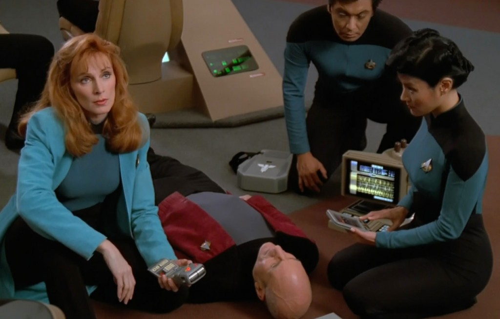 Captain Picard lays on the flow while crew members surround him with technology