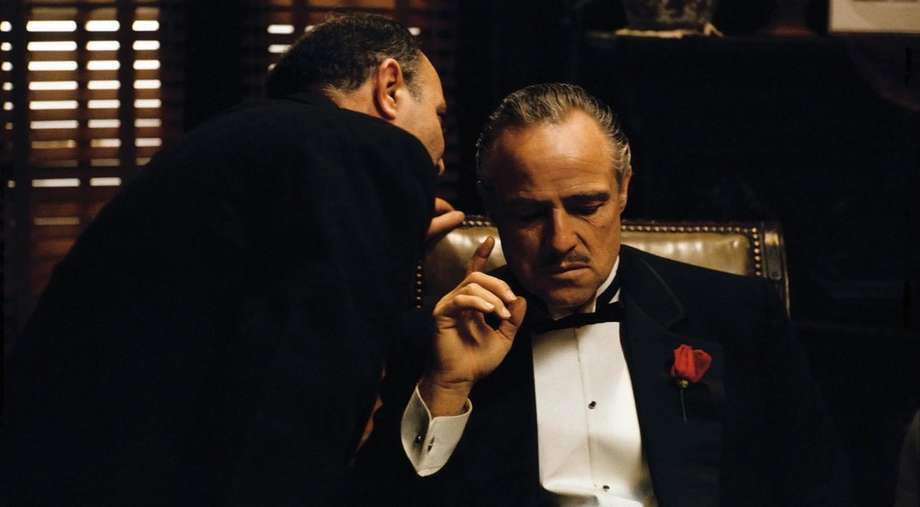 A scene from The Godfather where a man whispers in another mans ear while they're both wearing tuxedos
