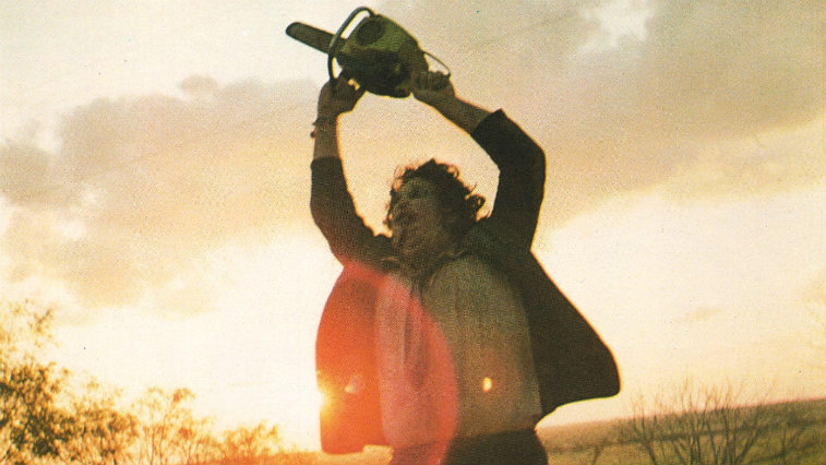 Gunnar Hansen as Leatherface in The Texas Chainsaw Massacre holding a chainsaw in the air