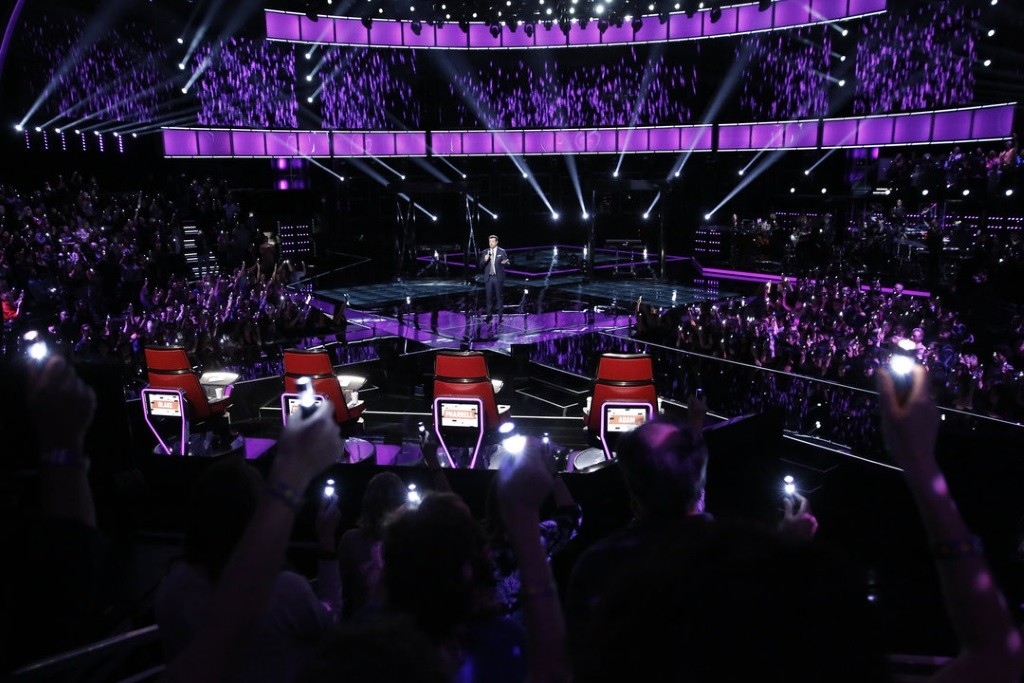 Carson Daly stands on the stage of the voice in front of the four coach chairs.