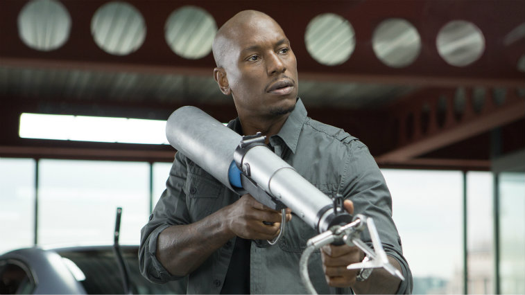 Tyrese Gibson is holding a large gun in Fast and Furious 6.