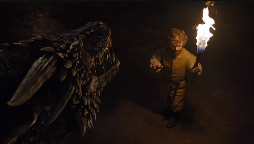 Tyrion approaches a dragon, while holding a torch