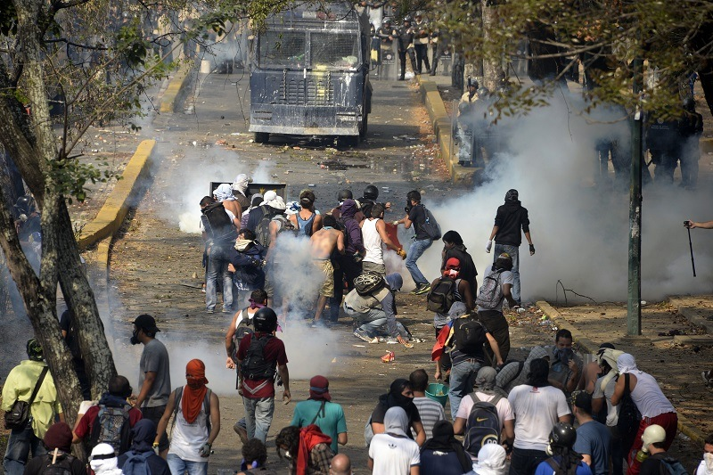 Venezuelan students clash with riot police during a protest against the government