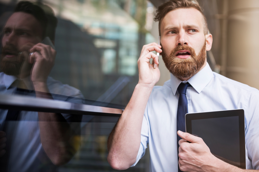 man blindsided by news at work on the phone