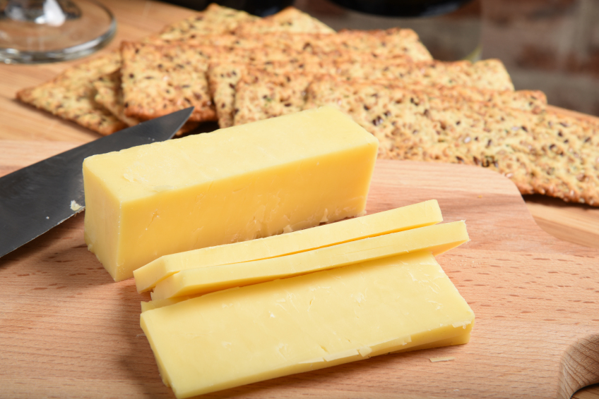 slicing white cheddar cheese ona cutting board with a knife