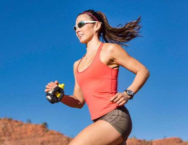 Woman running outdoors in fitness gear.