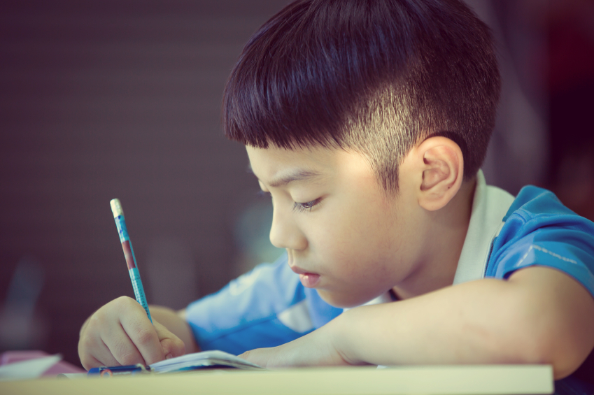 young boy writing a letter or doing his homework