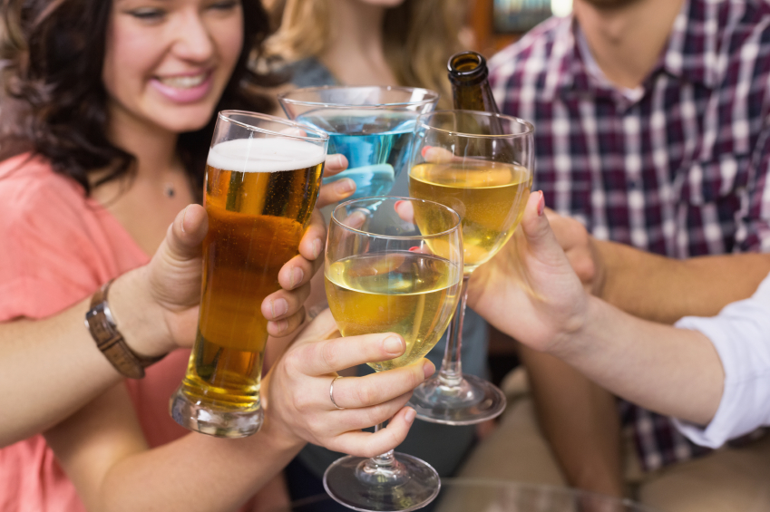 group of four friends clinking alcoholic beverages