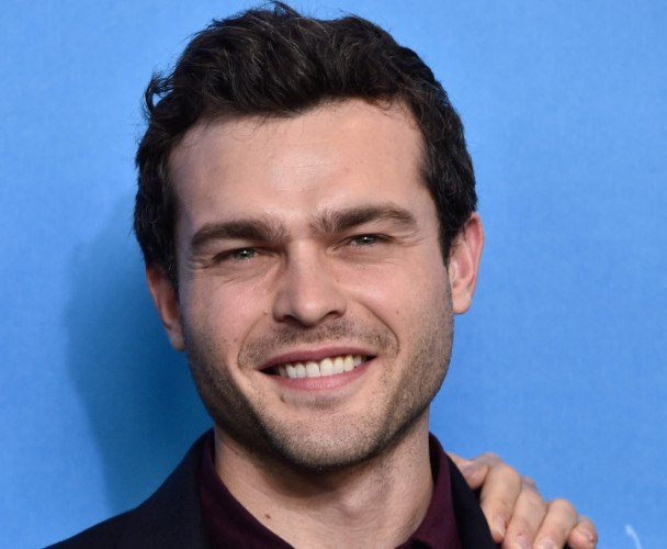 Alden Ehrenreich smiles while posing in front of a blue wall.