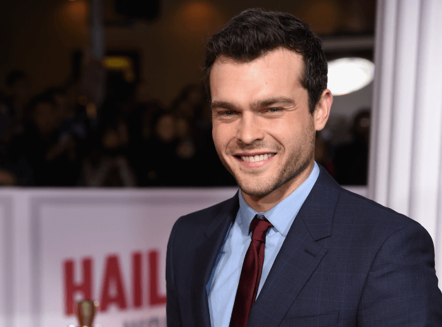 Alden Ehrenreich smiling while posing on a red carpet.
