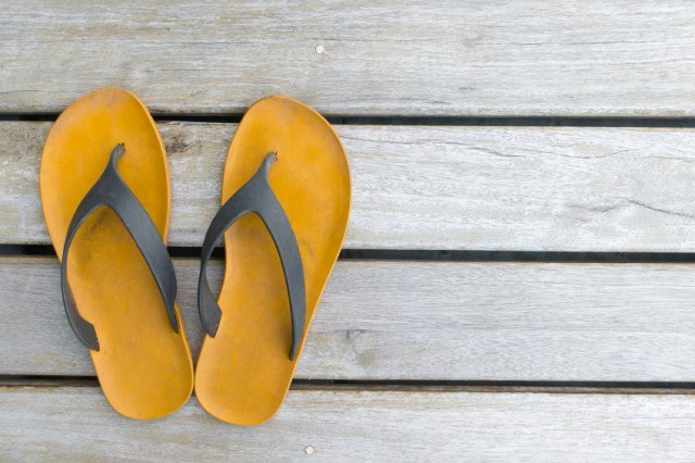 brown flip-flop sandals on a wooden background
