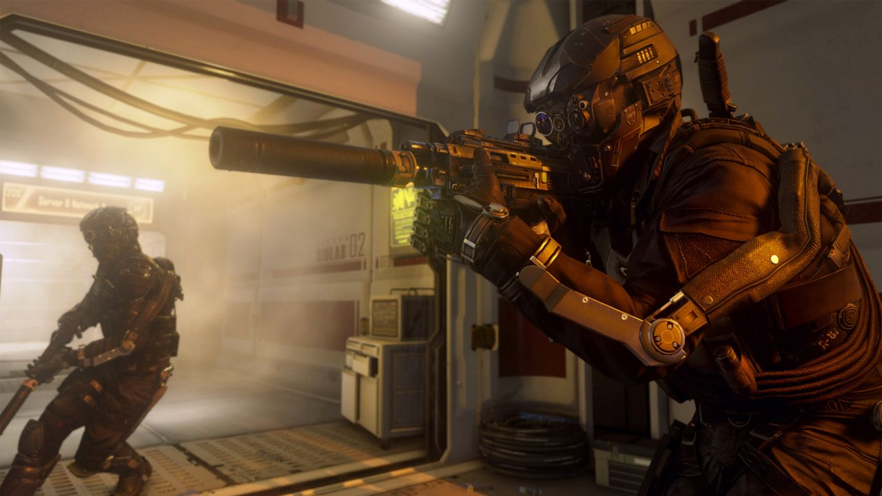 A soldier wearing a futuristic helmet aims a silenced rifle.