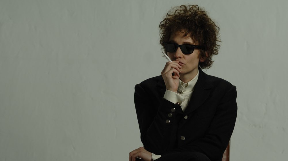 Cate Blanchett dressed as Bob Dylan, smoking a cigarette in sunglasses