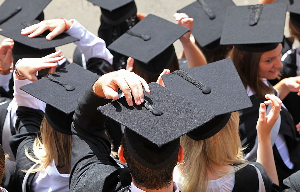 College graduates hold their caps