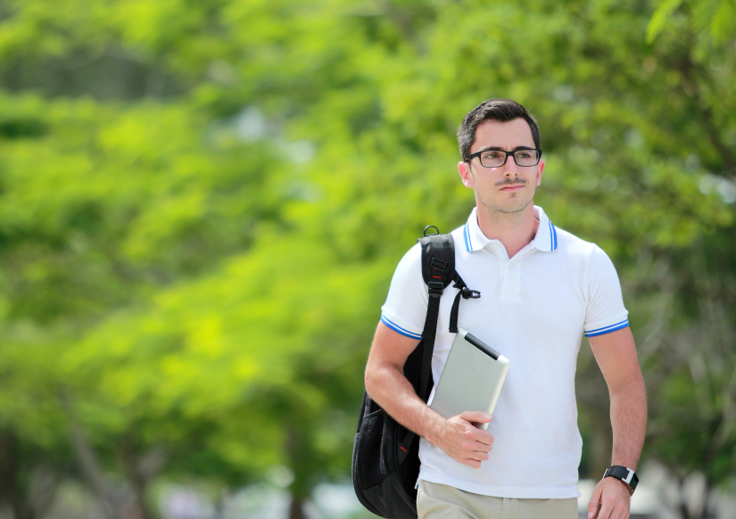 young man walking outside with a backpack over one shoulder
